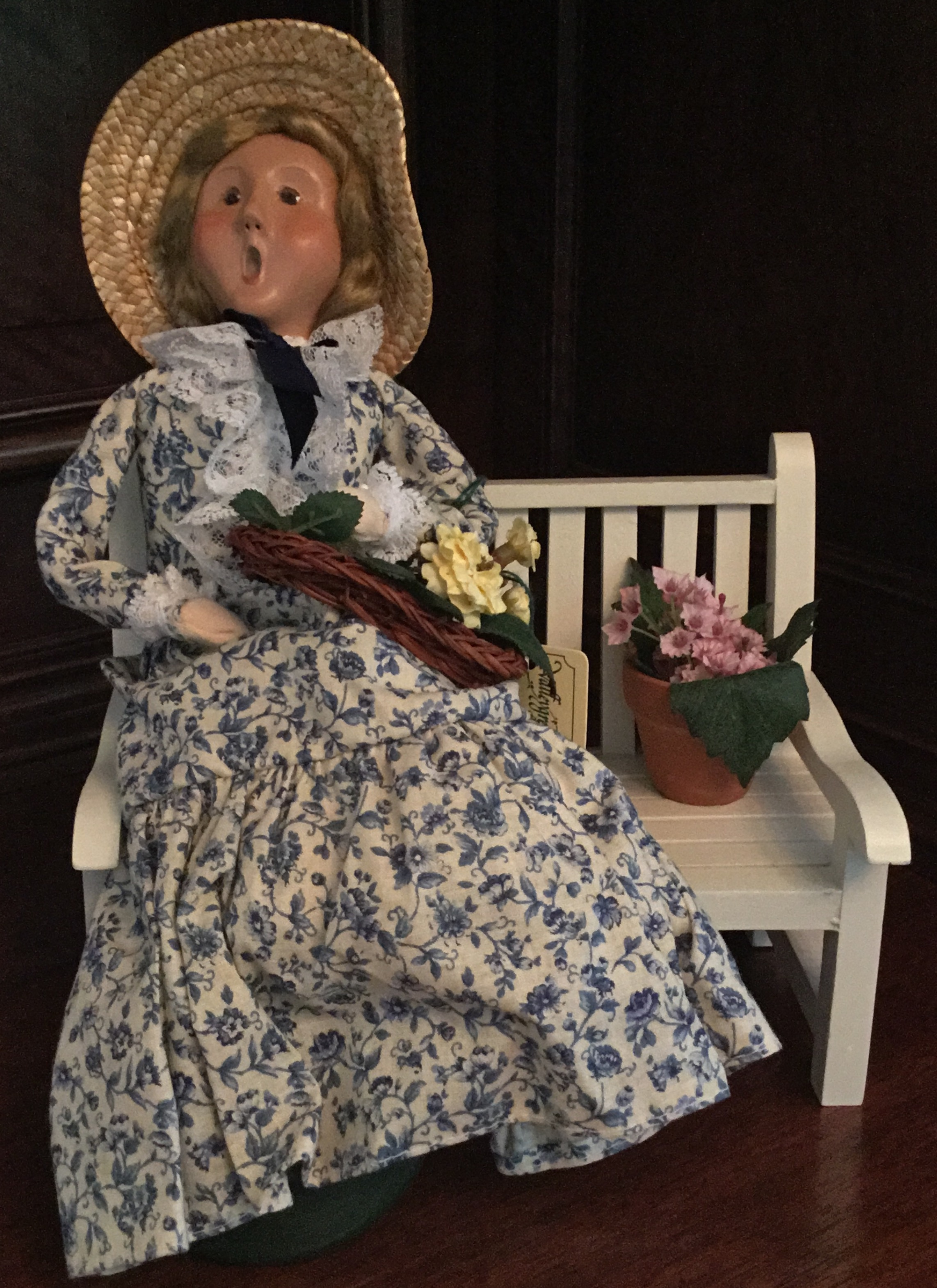 Byers' Choice, Woman with Flowers on White Bench